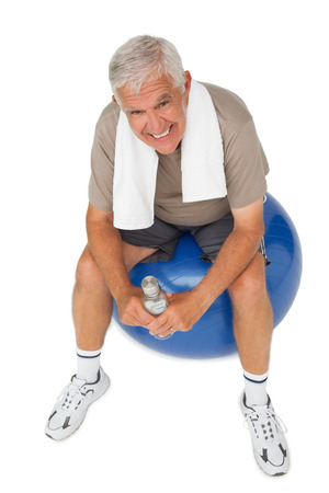Portrait of a happy senior man with water bottle sitting on fitness ball over white background photo