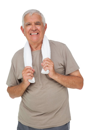 Portrait of a senior man with towel standing over white background photo