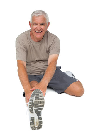 Full length portrait of a senior man stretching hands to leg over white background
