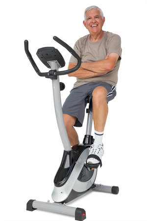 Full length portrait of a senior man on stationary bike over white background