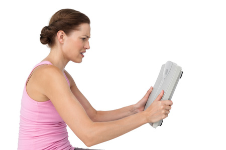 offended: Side view of an annoyed young woman with weight scale over white background