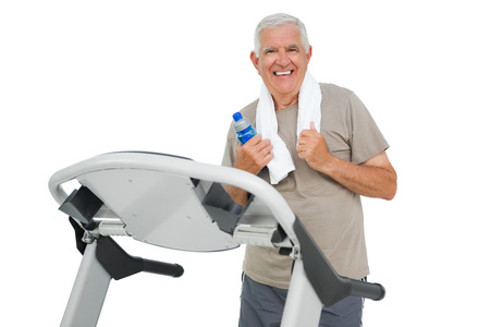 Happy senior man running on a treadmill over white background photo
