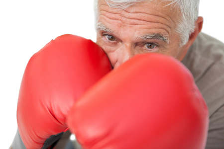 Close-up portrait of a determined senior boxer over white background photo