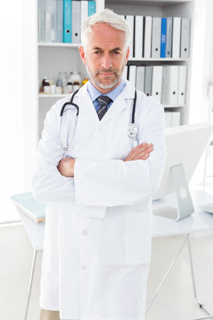 Portrait of a serious confident male doctor standing with arms crossed at medical office photo