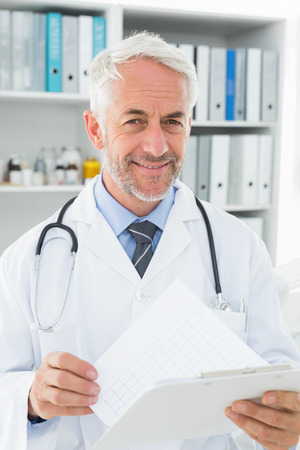 Portrait of a smiling male doctor with reports standing in the medical office photo