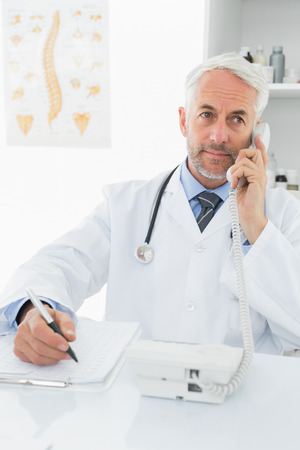 Concentrated male doctor writing reports while on call in the medical office photo