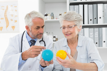 Male doctor showing stress buster balls to senior patient at the medical office photo