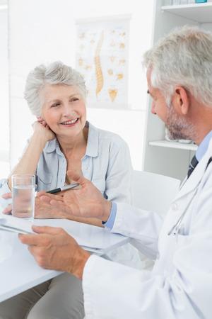 medico y paciente: Mujer senior paciente visitar a un médico en el consultorio médico