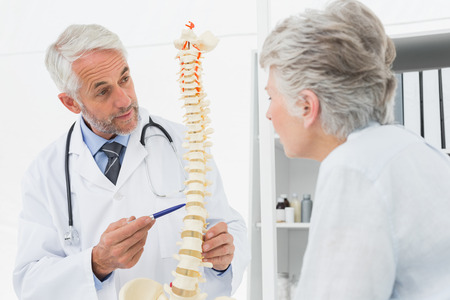 Male doctor explaining the spine to senior patient in medical office photo