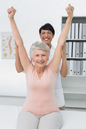 Portrait of female physiotherapist with senior woman raising hands in the medical office photo