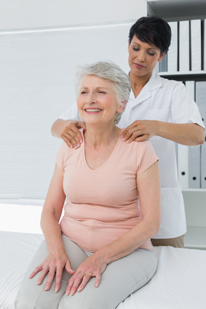 Female chiropractor massaging a senior womans shoulder in the medical office photo