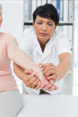 Female physiotherapist examining a senior patients hand in the medical office photo