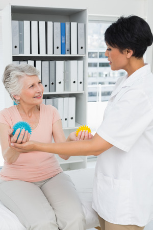 Female doctor with senior patient using stress buster balls at the medical office photo