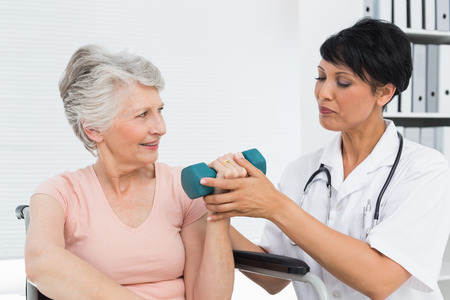 Female physiotherapist assisting senior woman to lift dumbbell in the medical office Stock Photo
