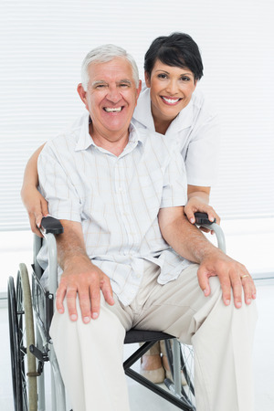 Portrait of a nurse with senior patient sitting in wheelchair at the hospital photo