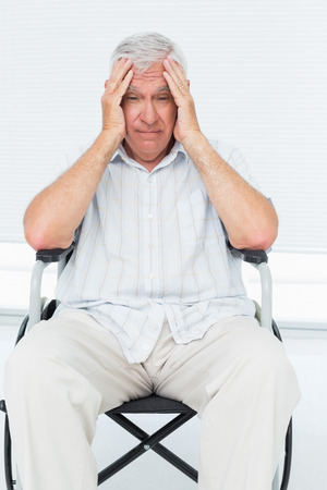 gloominess: Sad senior man sitting in wheelchair at the medical office Stock Photo