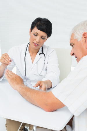 Female physiotherapist examining senior patients wrist with goniometer medical office photo