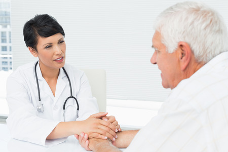 Female doctor holding senior patients hands at medical office photo