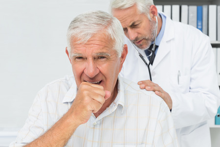 tosiendo: Paciente senior masculino visitar a un médico en el consultorio médico