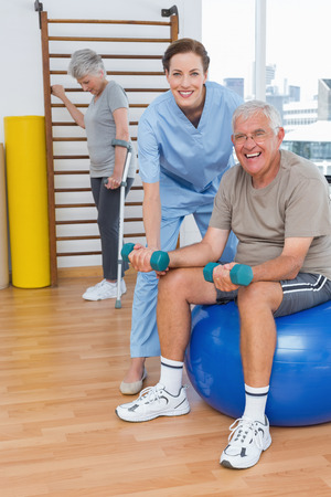 Female therapist assisting senior man with dumbbells in the medical office photo