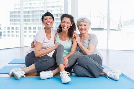 mujeres maduras: Longitud total de mujeres alegres que se sientan en la clase de yoga
