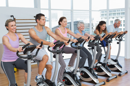 Group portrait of happy people working out at spinning class in gym photo