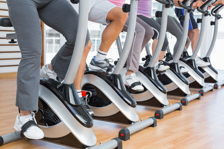 low section: Low section of sporty people working out at spinning class in gym Stock Photo