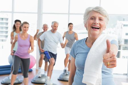 mujeres fitness: Mujer mayor alegre que gesticula los pulgares para arriba con la gente que ejercita en el fondo en el gimnasio