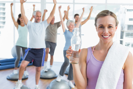 Young woman holding bottle with people stretching hands in the background at fitness studio photo