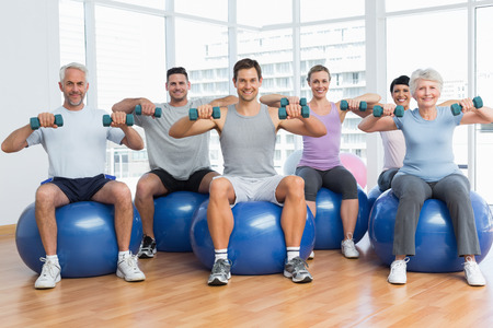 Portrait of fitness class with dumbbells sitting on exercise balls in a bright gym Stock Photo