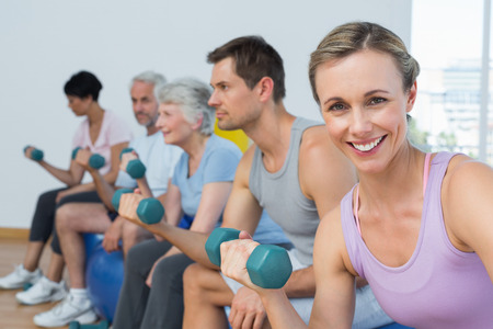 Side view of fitness class exercising with dumbbells in a bright gym photo