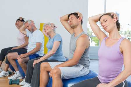 Fitness class sitting on exercise balls and stretching neck in a bright gym photo