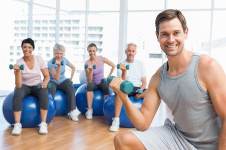 Portrait of fitness class with dumbbells sitting on exercise balls in a bright gym photo
