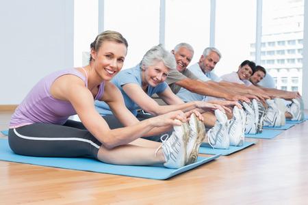 Gelukkig vrouwelijke trainer met klasse stretching handen naar benen op yogales Stockfoto