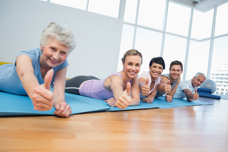 Fitness group gesturing thumbs up in row at the yoga class photo