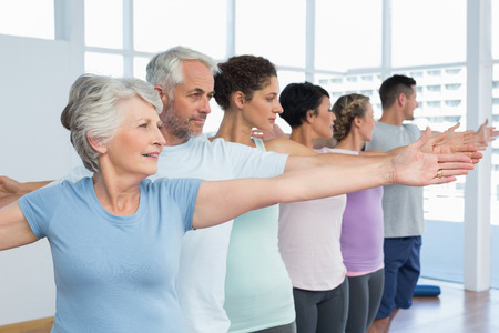 Portrait of fitness class stretching hands in row at yoga class photo
