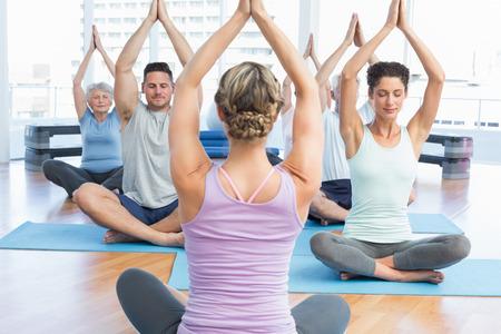 manos unidas: Los amantes del deporte con las manos unidas sobre las cabezas en el estudio de fitness