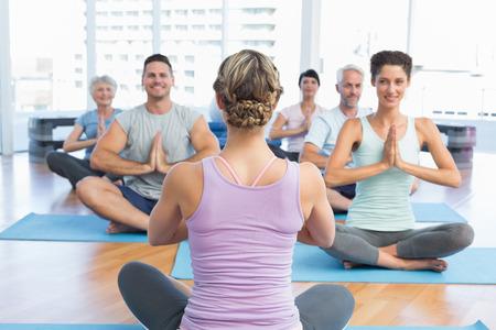manos unidas: Los amantes del deporte con las manos juntas, sentado en el estudio de fitness