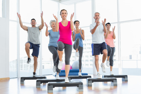 Portrait of smiling people doing power fitness exercise at yoga class in fitness studio Banco de Imagens - 27197088
