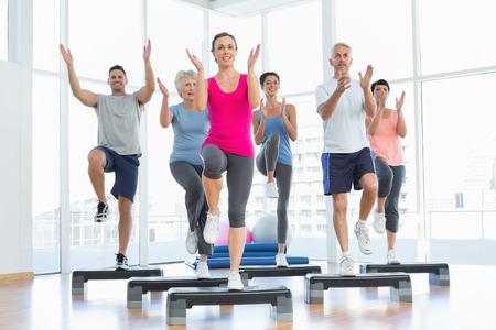 Portret van lachende mensen die de macht fitness oefening op yogales in fitness-studio Stockfoto