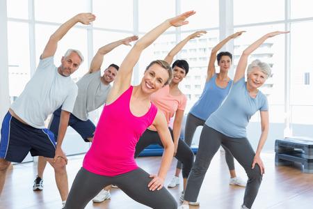 ヨガのクラスに手を伸ばすクラスと幸せな女性のトレーナー