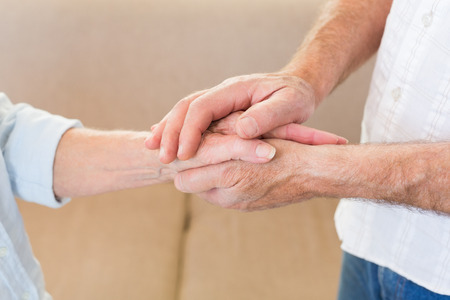 touching hands: Retired couple touching hands at home in living room Stock Photo
