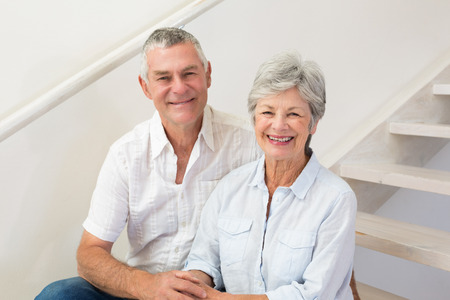 domiciles: Senior couple sitting on stairs smiling at camera at home in living room