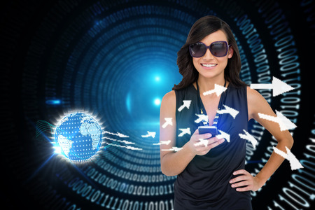 Digital composite of glamorous brunette using smartphone with earth and arrows photo