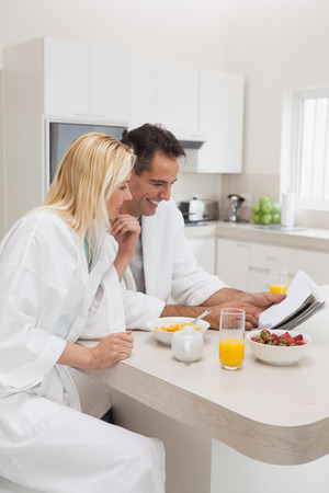 Couple in bathrobes having breakfast while reading newspaper in the kitchen at home photo
