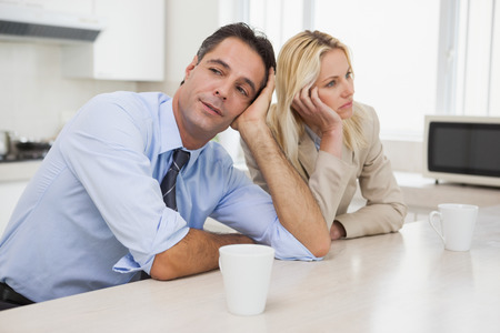 Unhappy business couple not talking after an argument in the kitchen at home photo