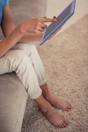 Low section of a young woman using digital tablet in the living room at home photo