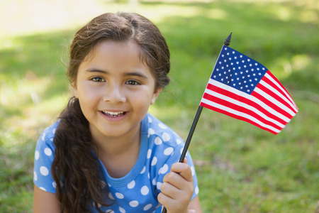 waving: Close-up portrait of a young girl holding the American flag at the park