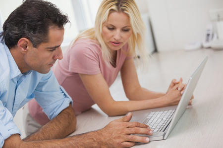 Side view of a couple using laptop in the kitchen at home photo