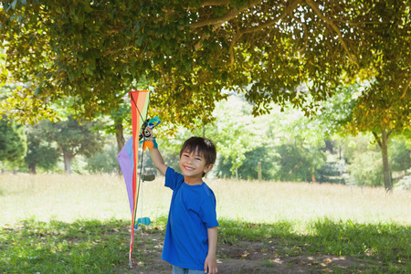 Full length portrait of a happy young boy holding kite at the park photo
